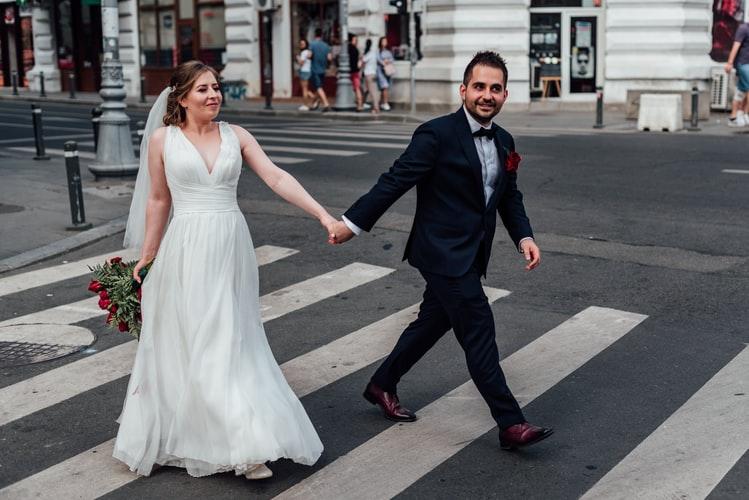 couple posing on a crossroad for their prenup photos