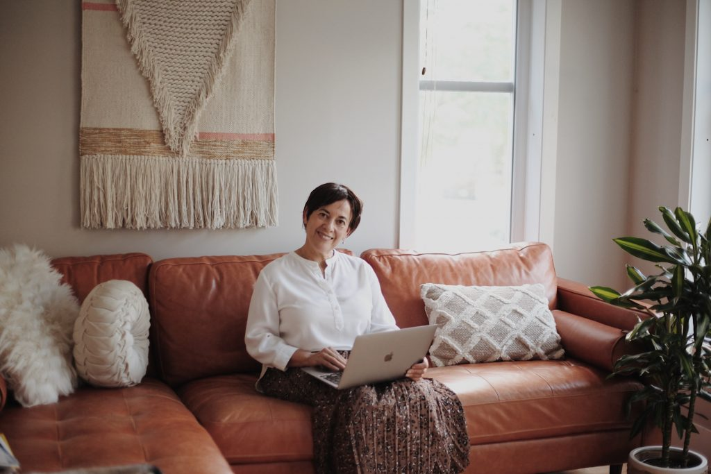 Woman sitting in an Italian furniture while working on her laptop